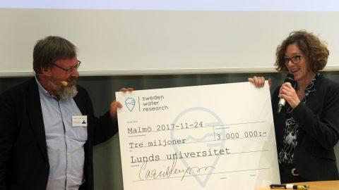 Kenneth M Persson lämnar över checken på 3 miljoner SEK till Lunds universitets Stacey Sörensen