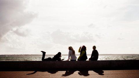 Fyra sittande kvinnor på rad vid havet.