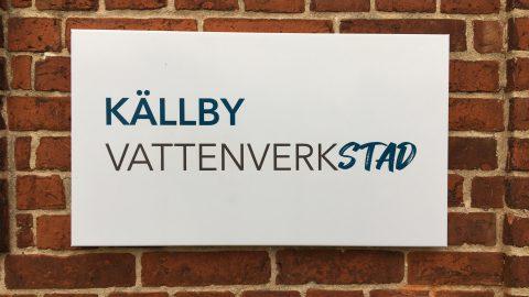 Bild på skylt mot tegelvägg. På skylten står det Källby vattenverksatd.