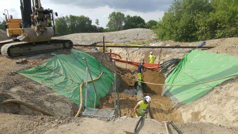 Bild på grävd grop med ledningar och 3 personer som arbetar. Personerna bär skyddshjälm och gula tröjor.